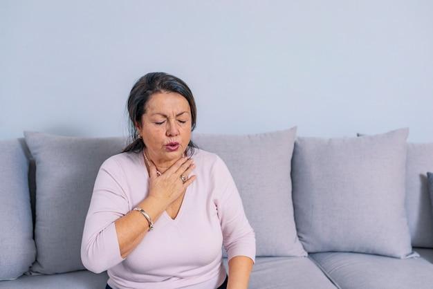 Ältere frau zu hause, die sich unwohl fühlt. eine ältere frau, die ihren hals berührt. Premium Fotos