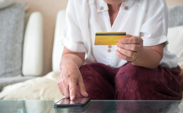 Ältere frauen, die online mit smartphone und kreditkarte von zu hause aus einkaufen. Premium Fotos