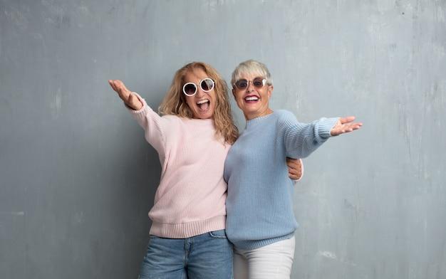 Ältere freunde der kühlen frauen gegen schmutzzementwand. Premium Fotos