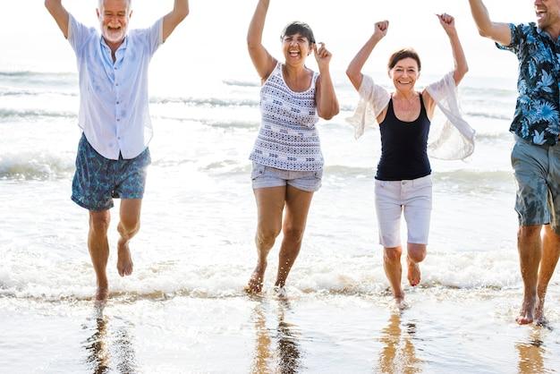 Ältere freunde, die am strand spielen Premium Fotos