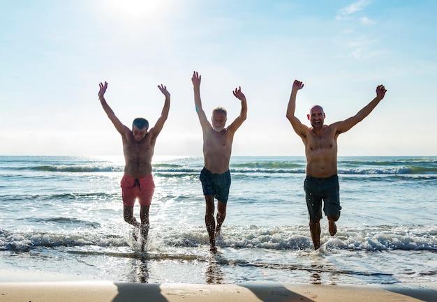 Ältere freunde, die den strand in der sommerzeit genießen Premium Fotos