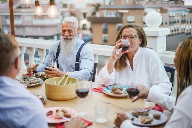 Ältere gemischtrassige leute, die spaß beim abendessen auf der terrasse haben Premium Fotos