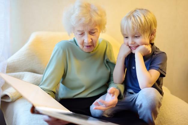 Ältere großmutter und kleines enkelkind, die familienfotoalbum schauen. oma und enkel. Premium Fotos