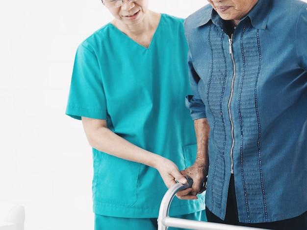 Ältere krankenschwester hilfe ältere frau mit walker. Premium Fotos