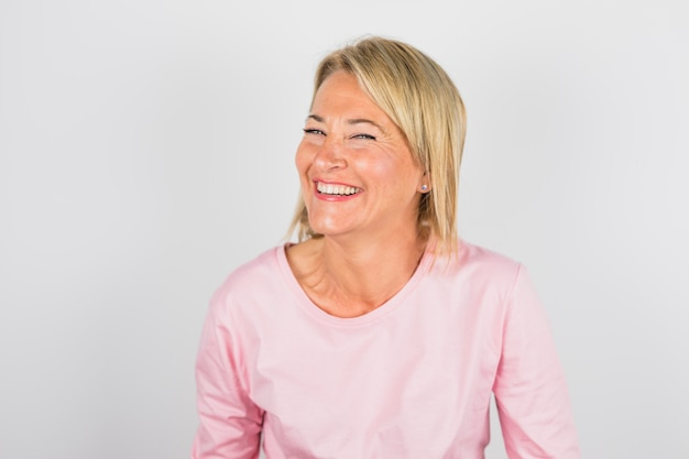 Ältere lachende frau in der rosafarbenen bluse Kostenlose Fotos