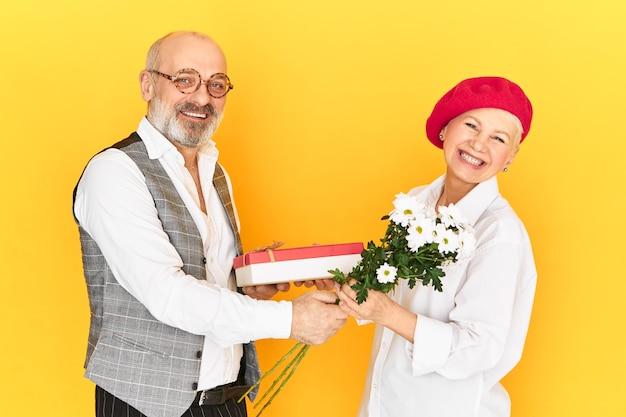 Ältere menschen, alter, dating, romantik und beziehungskonzept. aufgeregte verwirrte frau mittleren alters in roter haube, die sich unbehaglich fühlt, während sie unerwartetes geschenk und blumen von einem älteren bärtigen mann erhält Kostenlose Fotos