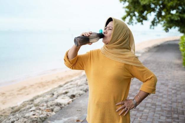 Ältere muslimische frau trinken wasser Premium Fotos