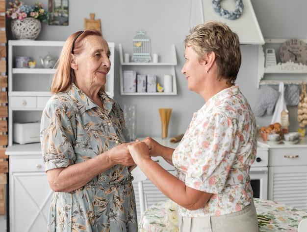 Ältere mutter und reife tochter, die hand in der küche zusammenhält Kostenlose Fotos