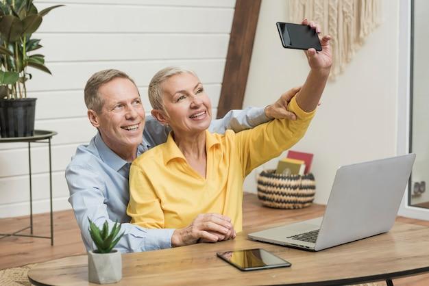 Ältere paare des smiley, die ein selfie nehmen Kostenlose Fotos
