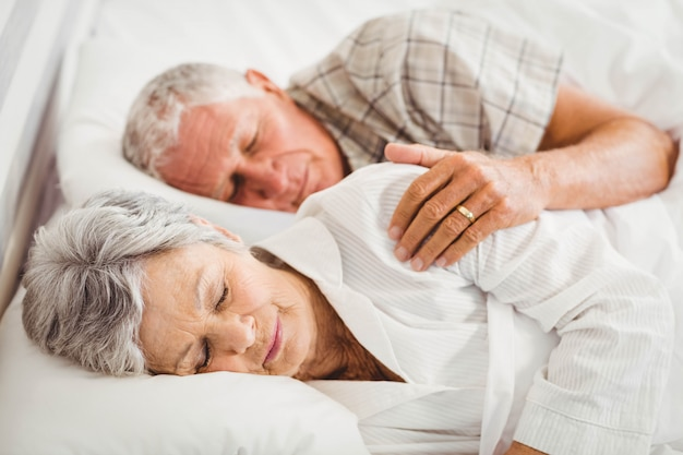 Ältere paare, die auf bett im schlafzimmer schlafen Premium Fotos