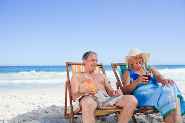 Ältere paare, die auf klappstühlen sitzen Premium Fotos
