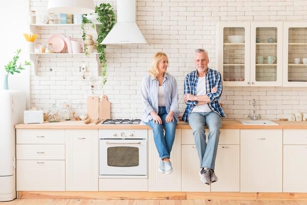 Ältere paare, die auf küchenarbeitsplatte sitzen Kostenlose Fotos