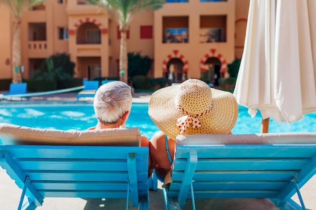 Ältere paare, die durch swimmingpool sich entspannen. die menschen genießen den urlaub. valentinstag Premium Fotos