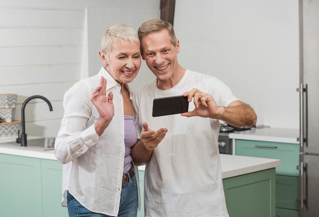 Ältere paare, die ein selfie in der küche nehmen Kostenlose Fotos