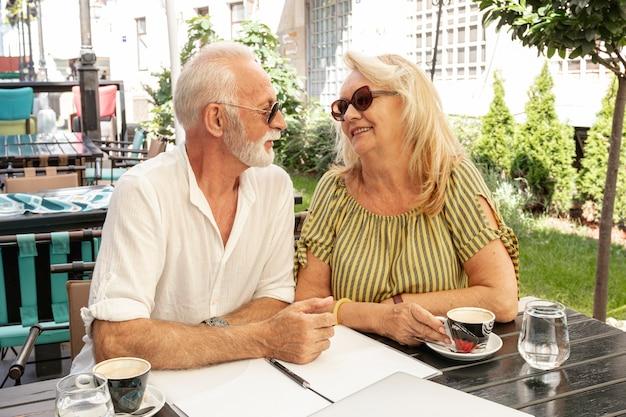 Ältere paare, die einander beim lächeln betrachten Kostenlose Fotos