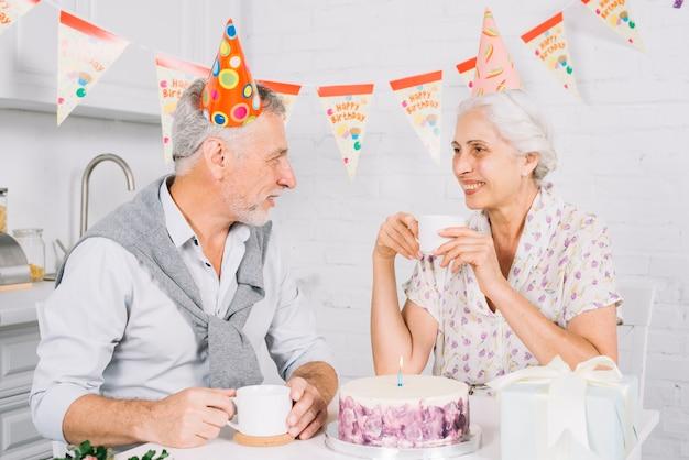 Ältere paare, die einander beim trinken des tasse kaffees während der geburtstagsfeier betrachten Kostenlose Fotos