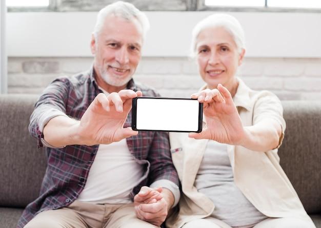 Ältere paare, die einen smartphone zeigen Kostenlose Fotos