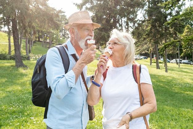 Ältere paare, die eiscreme in einem park essen Kostenlose Fotos