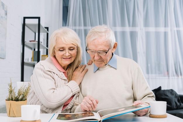 Ältere paare, die fotoalbum betrachten Kostenlose Fotos