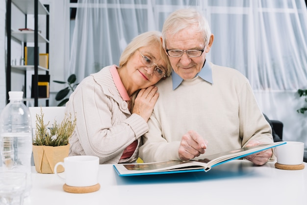 Ältere paare, die fotoalbum betrachten Premium Fotos