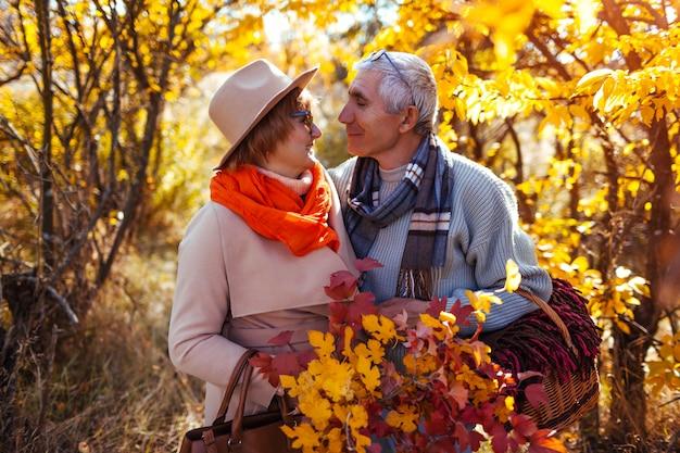 Ältere paare, die im herbstwald umarmen und draußen kühlen Premium Fotos