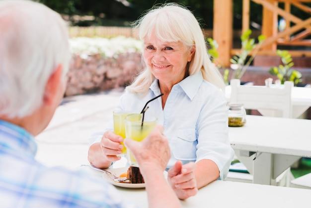 Ältere paare, die orangensaft auf freienveranda trinken Kostenlose Fotos