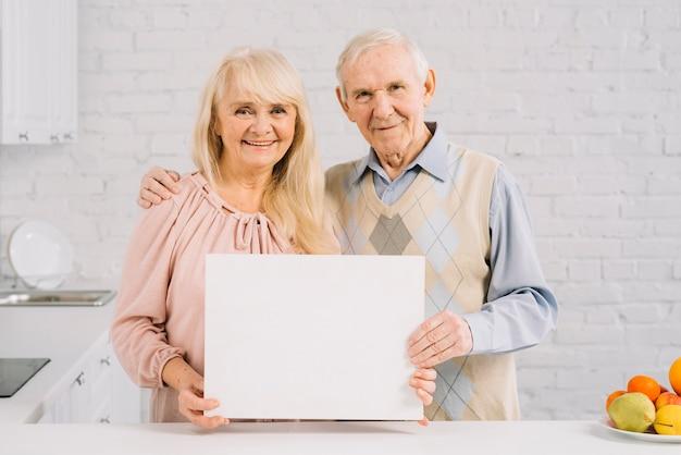 Ältere paare, die schablone in der küche halten Kostenlose Fotos