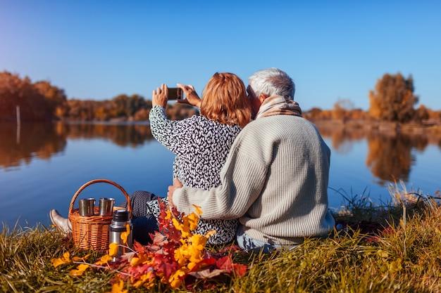 Ältere paare, die selfie beim haben des picknicks durch herbstsee nehmen. Premium Fotos