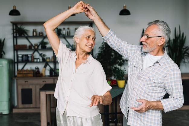 Ältere paare, die tanzen im haus genießen Kostenlose Fotos