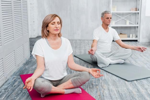 Ältere paare, die zu hause meditation auf übungsmatte durchführen Kostenlose Fotos