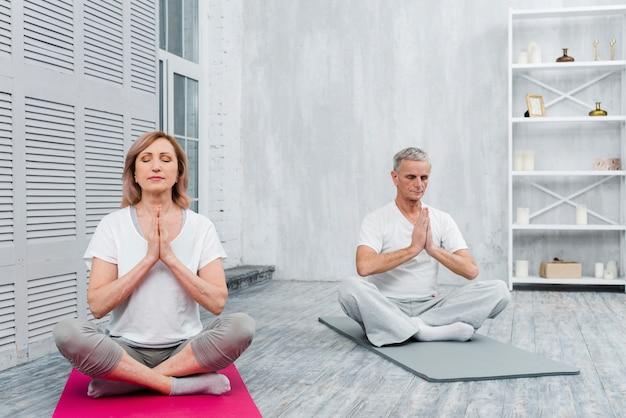 Ältere paare, die zu hause mit den betenden händen auf yogamatte meditieren Kostenlose Fotos