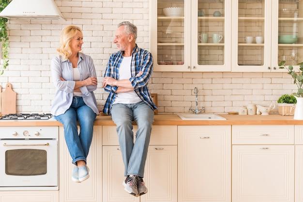 Ältere paare mit seinem arm kreuzten das sitzen auf der küchenarbeitsplatte, die einander betrachtet Kostenlose Fotos