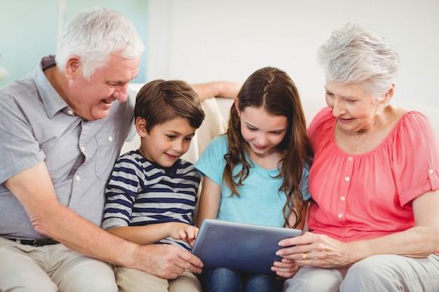 Ältere paare und ihre großartigen kinder, die digitale tablette im wohnzimmer verwenden Premium Fotos