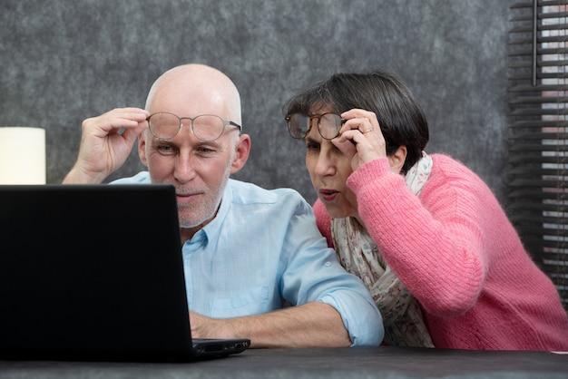 Ältere paare unter verwendung des laptops, sie haben schwierigkeiten und sichtprobleme Premium Fotos