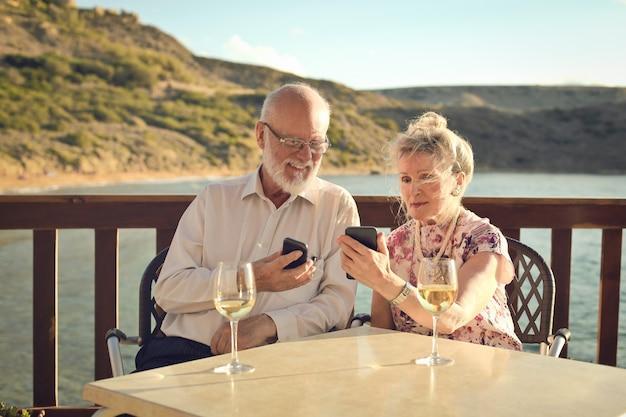 Ältere paare unter verwendung des smartphone auf ferien Premium Fotos