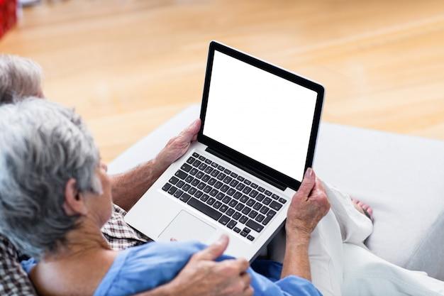 Ältere paare unter verwendung einer digitalen tablette auf sofa Premium Fotos