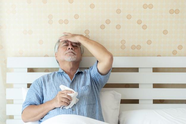 Ältere patienten im bett, asiatische ältere mannpatienten-kopfschmerzenhände auf stirn Premium Fotos