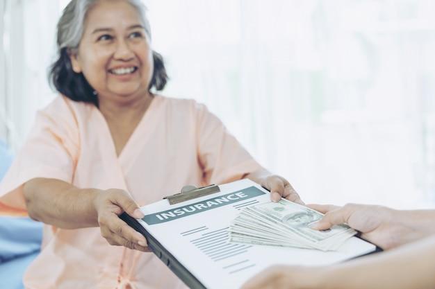 Ältere patienten verletzen frau auf patientenbett im krankenhaus, das uns dollarnoten hält, fühlen sich glücklich, versicherungsgeld von versicherungsunternehmen zu erhalten Kostenlose Fotos