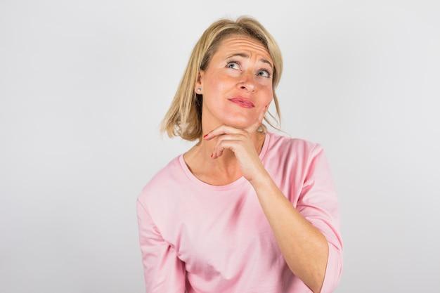 Ältere reizend nachdenkliche frau in der rosafarbenen bluse Kostenlose Fotos