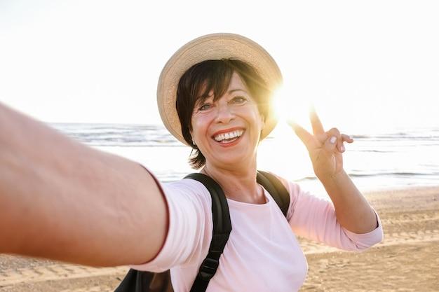 Ältere schöne frau mit hut und rucksack lächelnd und ein selfie am strand nehmend Premium Fotos