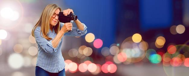 Ältere schönheit mit einer weinlesekinokamera Premium Fotos