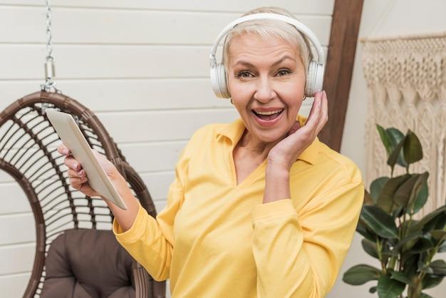 Ältere smileyfrau, die musik zwar kopfhörer hört Kostenlose Fotos