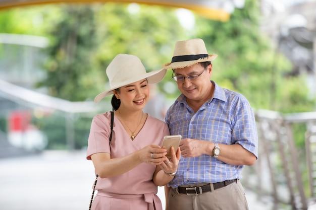 Ältere touristen, die am mobiltelefon schauen Premium Fotos