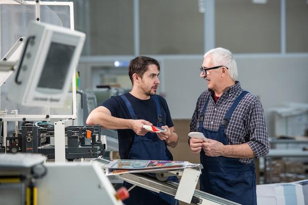 Ältere und junge arbeiter, die am industriedrucker stehen und druckfarben diskutieren, während sie farbpalette betrachten Premium Fotos