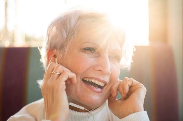 Ältere weibliche hörende musik des smiley Kostenlose Fotos