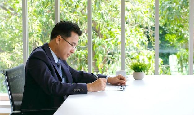 Älterer asiatischer geschäftsmann, der an dokument an seinem schreibtisch arbeitet Premium Fotos