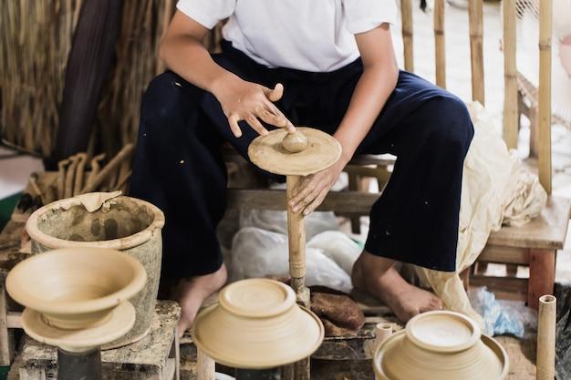 Älterer asiatischer handcraft töpfer, der eigenhändig tongefäßerdwaren herstellt. Premium Fotos