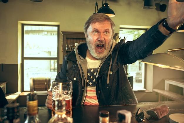 Älterer bärtiger mann, der alkohol in der kneipe trinkt und ein sportprogramm im fernsehen sieht. ich genieße meinen lieblingsbrot und mein lieblingsbier. mann mit bierkrug, der am tisch sitzt. Kostenlose Fotos