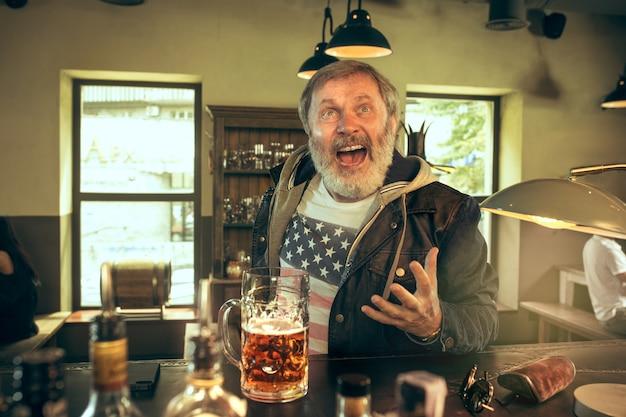Älterer bärtiger mann, der alkohol in der kneipe trinkt und ein sportprogramm im fernsehen sieht. Kostenlose Fotos