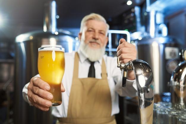 Älterer barmann, der kaltes glas mit lagerbier hält Premium Fotos